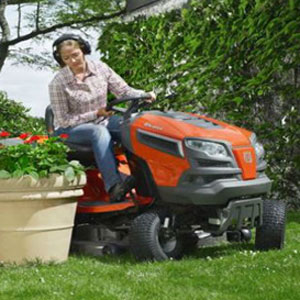 Woman riding on Husqvarna lawn tractor