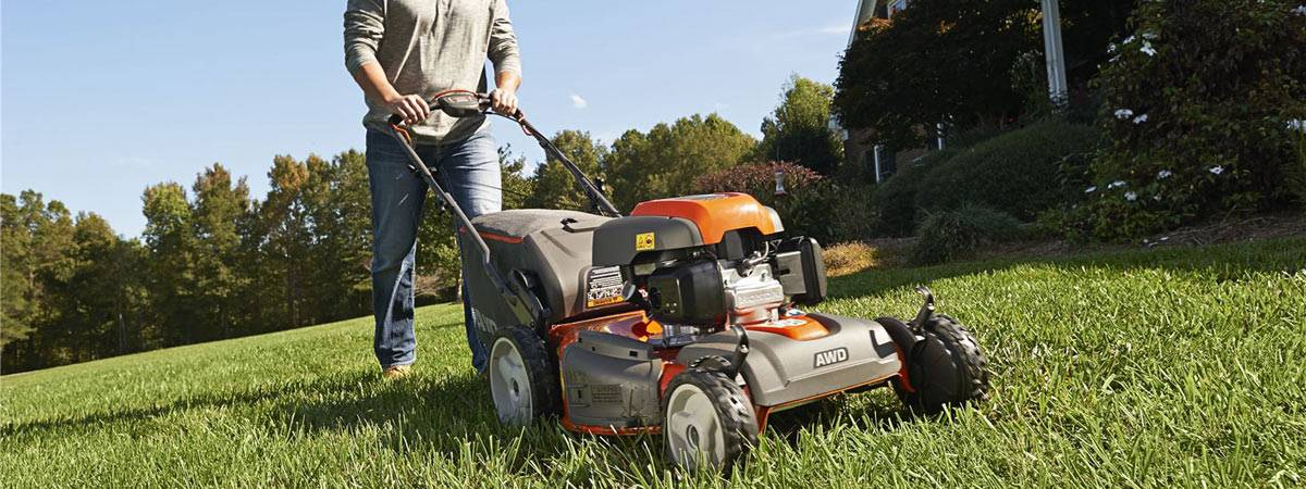 Man pushing Husqvarna Lawn Mower