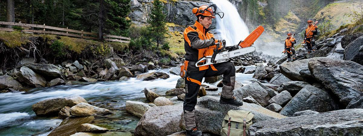 Man holding Stihl chainsaw by river