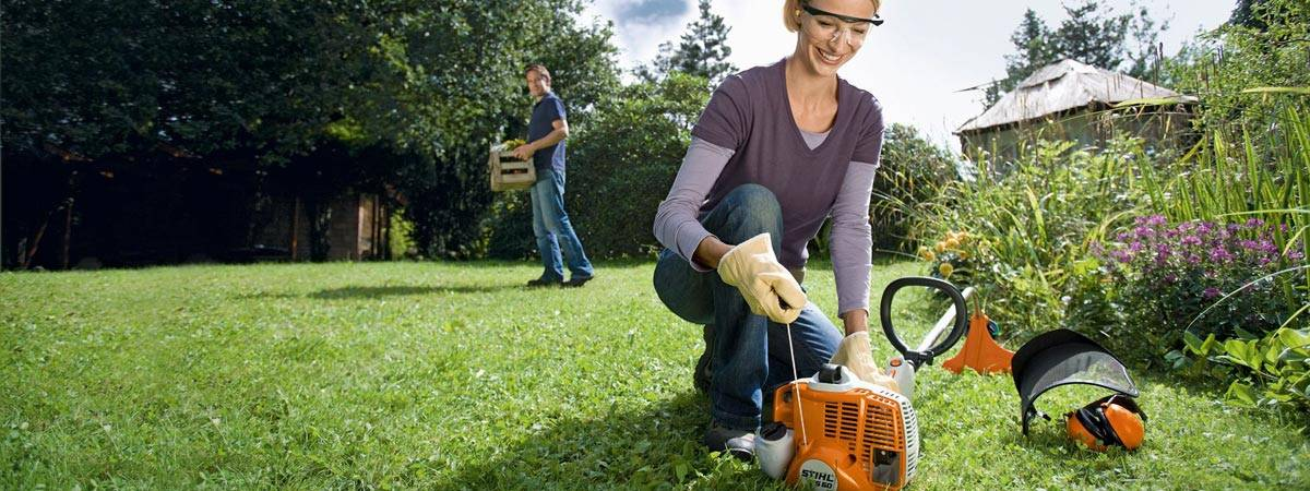 Woman starting Stihl Weed Eater in garden